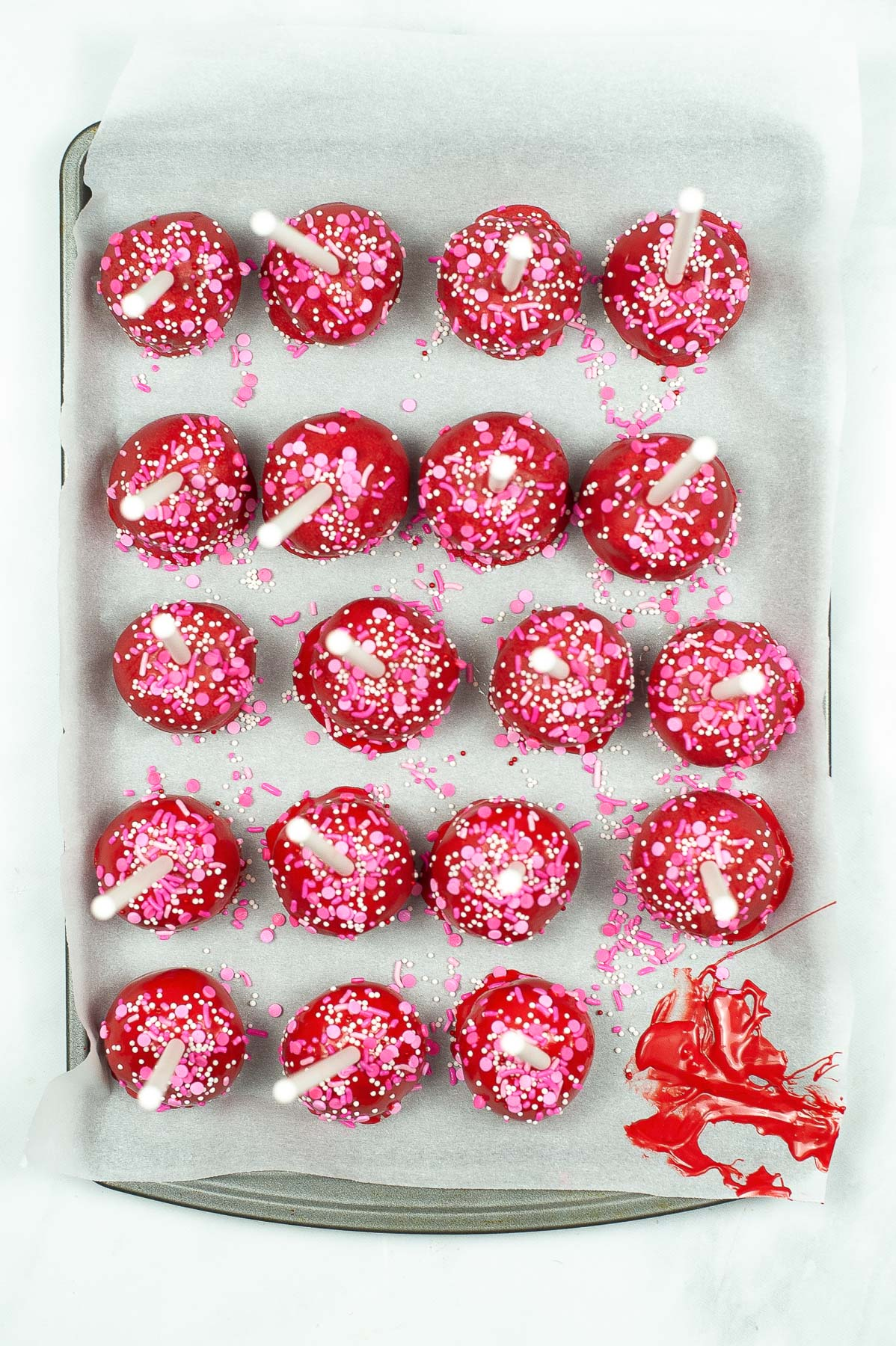 red cake pops drying on parchment paper
