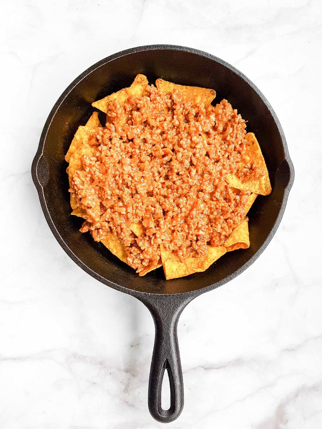 tortilla chips topped with cooked ground beef in a skilet