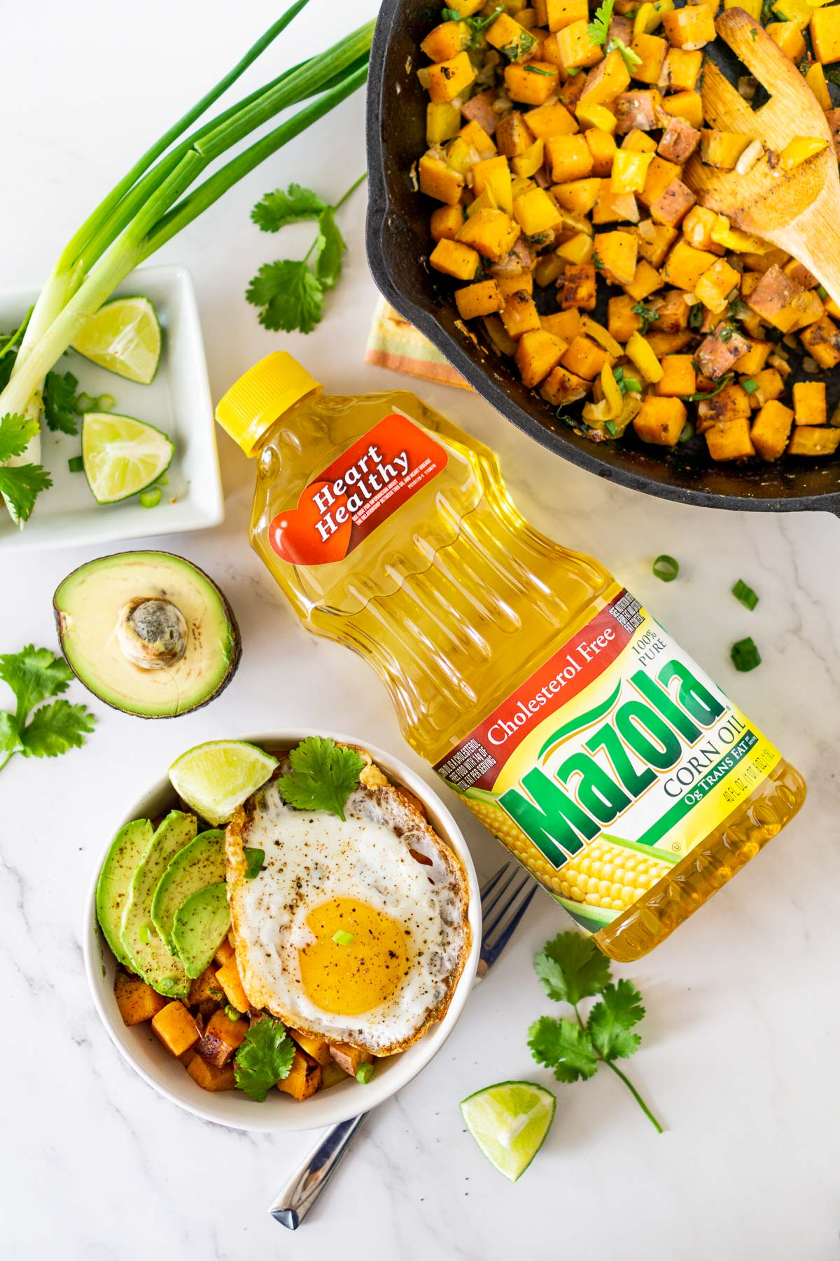 bowl of sweet potato breakfast hash with a bottle of corn oil next to it