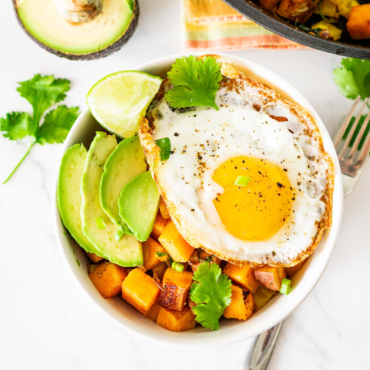 bowl of sweet potato hash with a fried egg on top with avocado