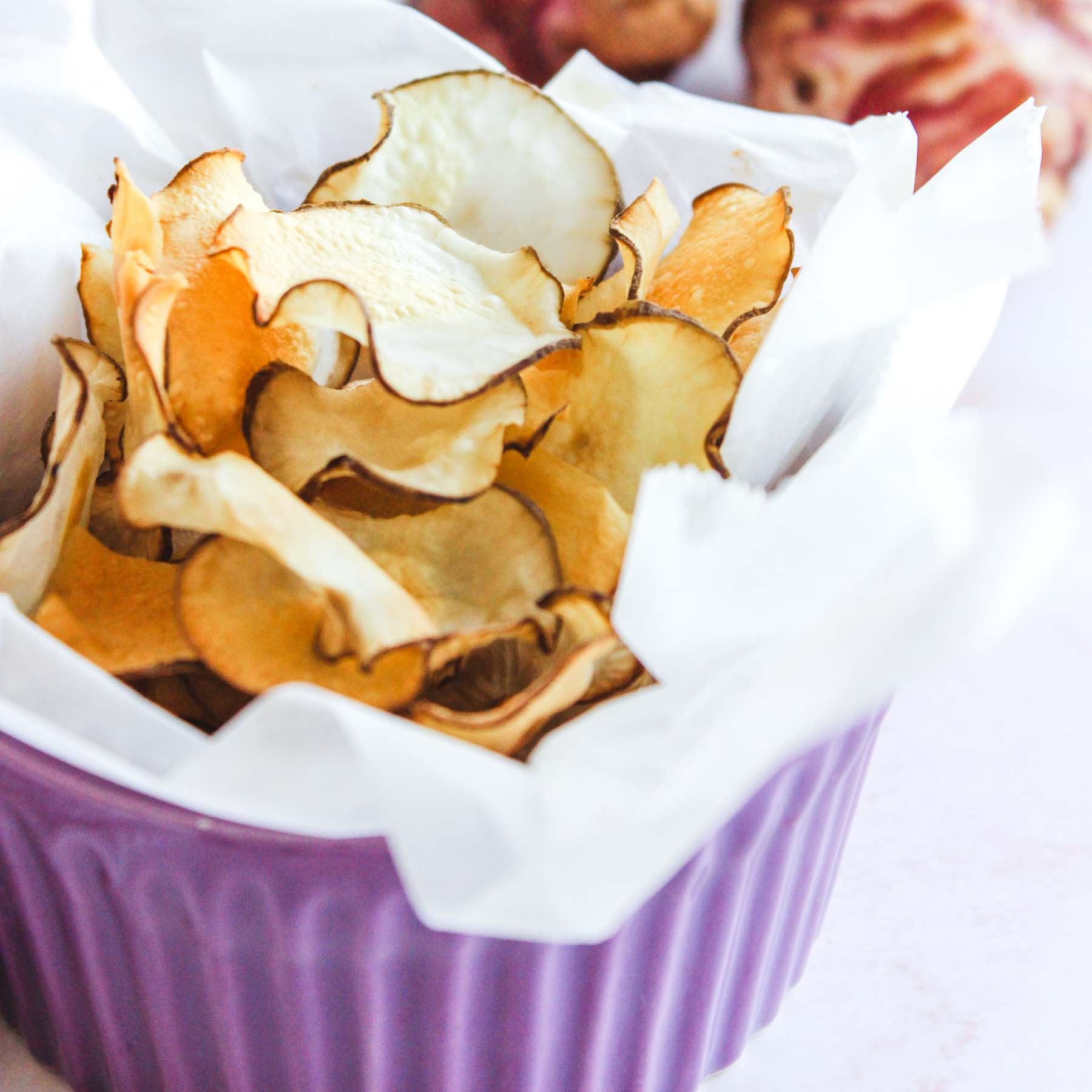 Baked jerusalem artichoke chips in a bowl.