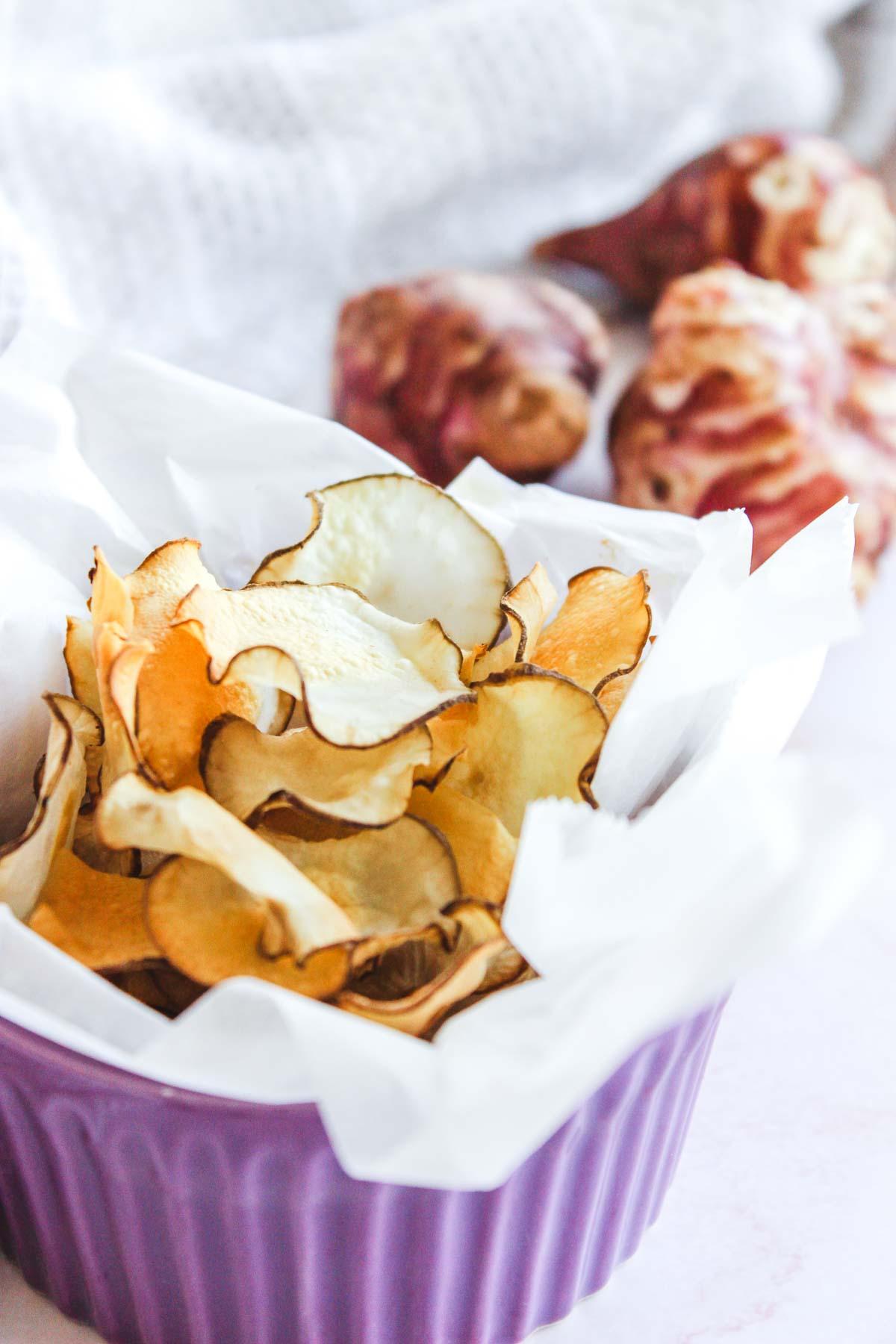 Bowl of crispy gluten-free jerusalem artichoke chips.
