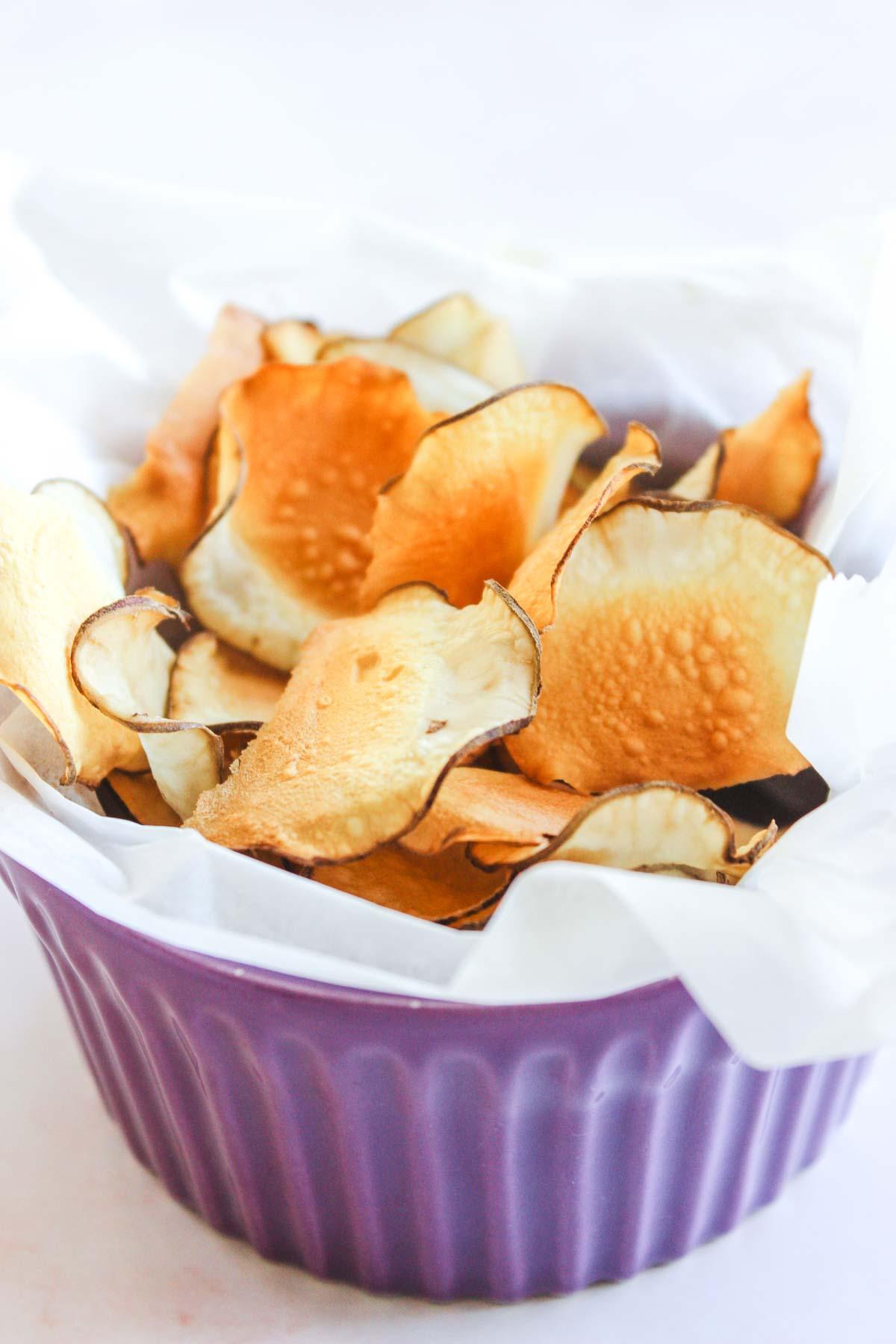 Bowl of golden crispy sunchoke chips.