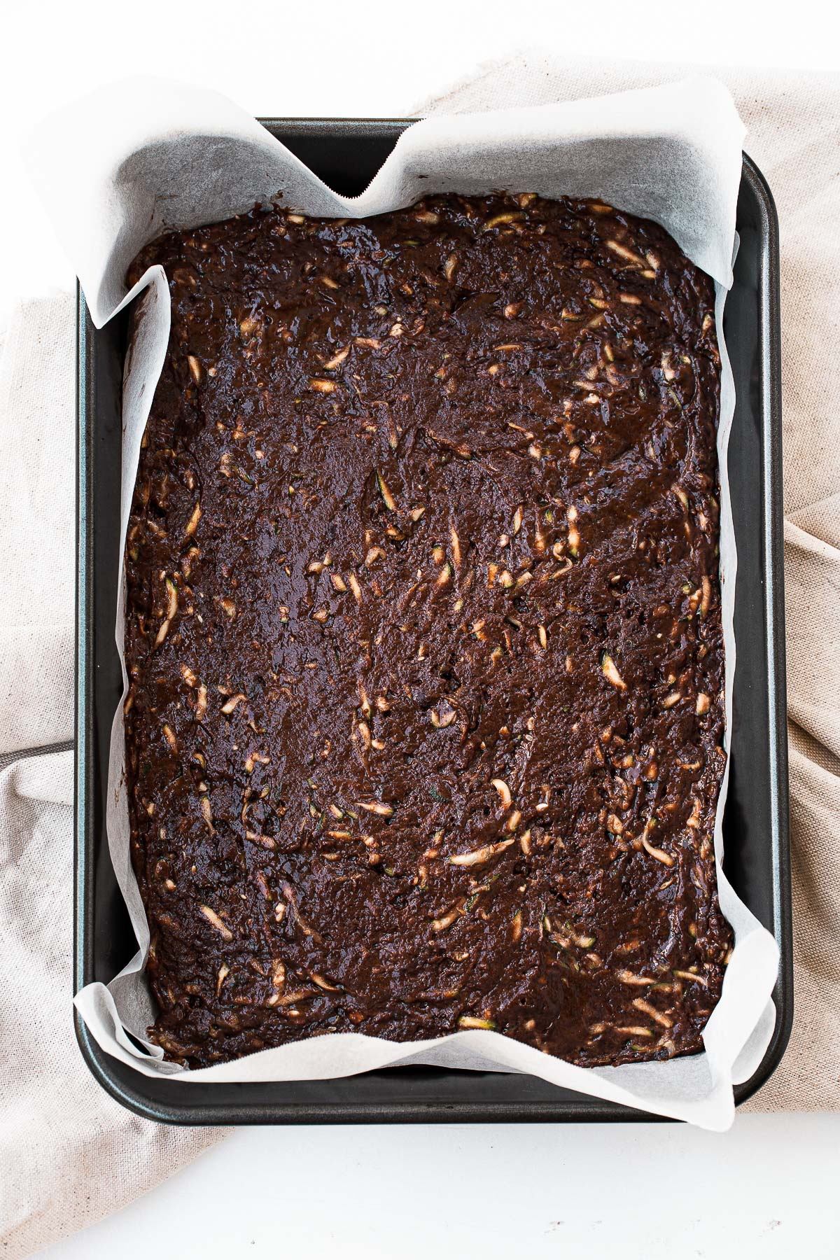 Brownie batter with zucchini in a baking dish.