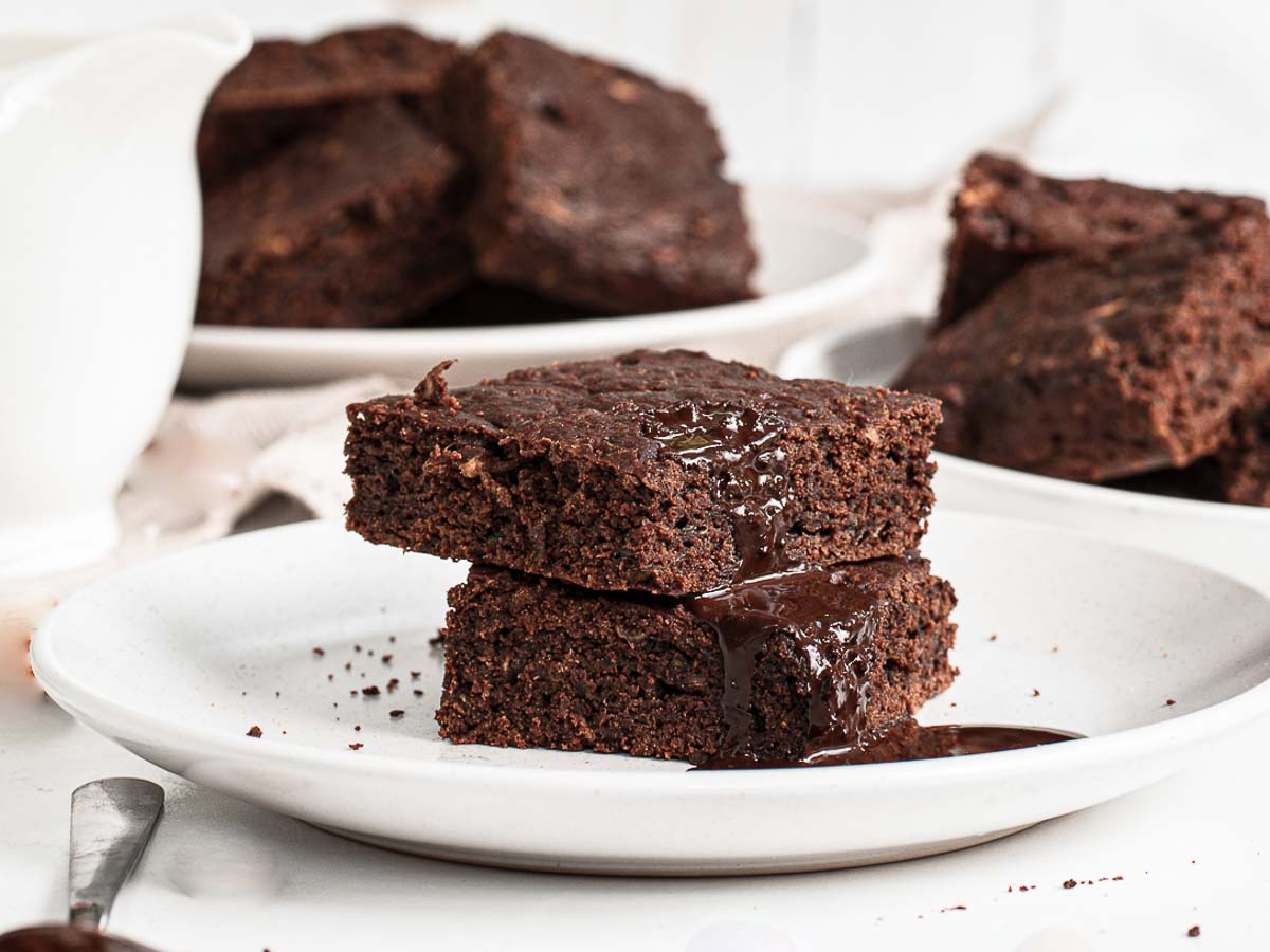 Stack of 2 zucchini brownies on a plate.