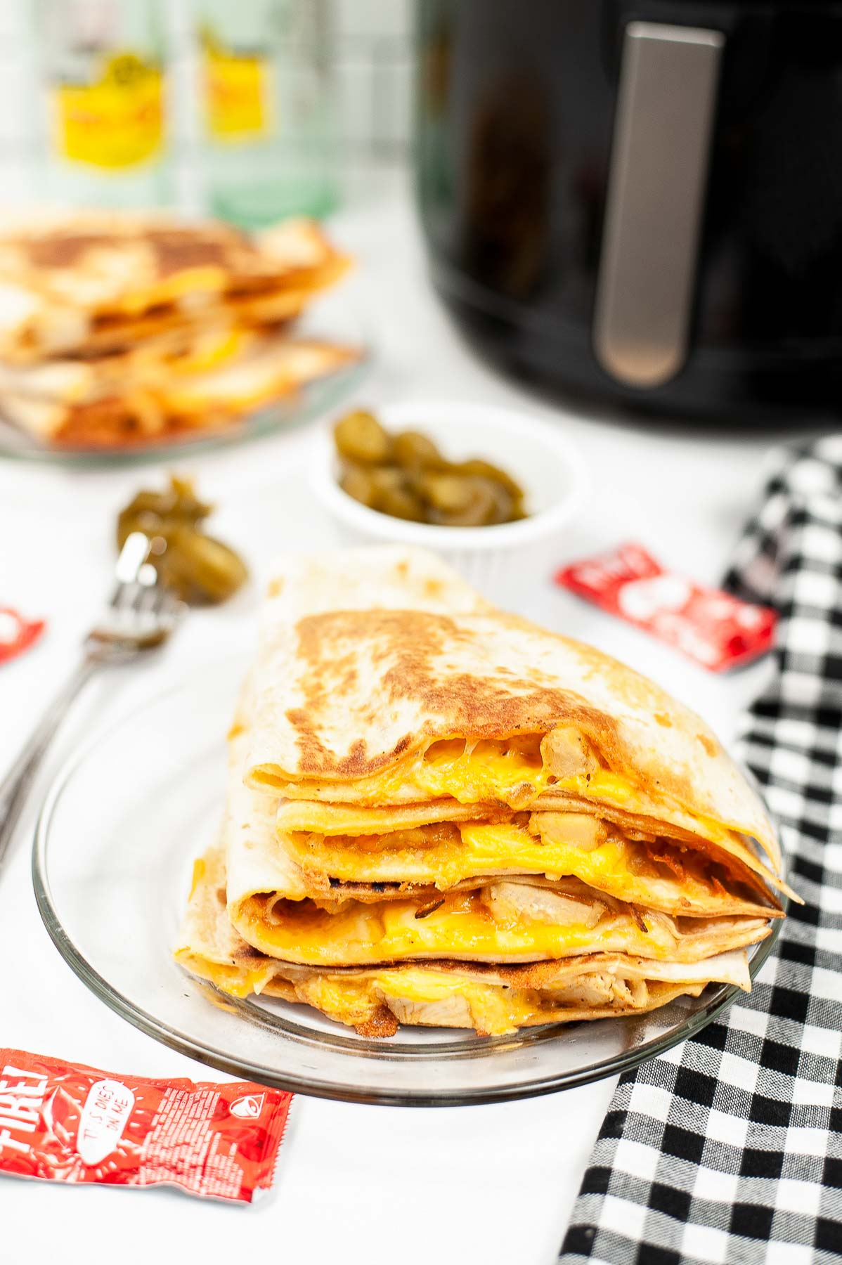 Taco bell chicken quesadilla on a plate next to air fryer and garnish.