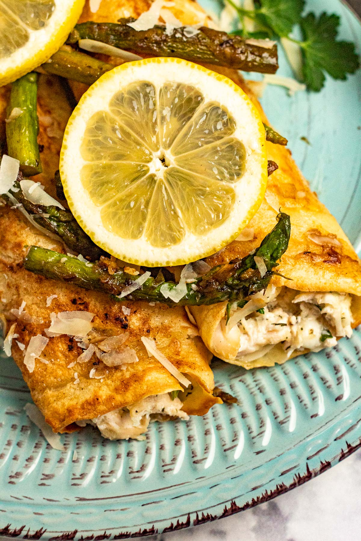 Savory chicken crepes topped with asparagus and lemon slices.