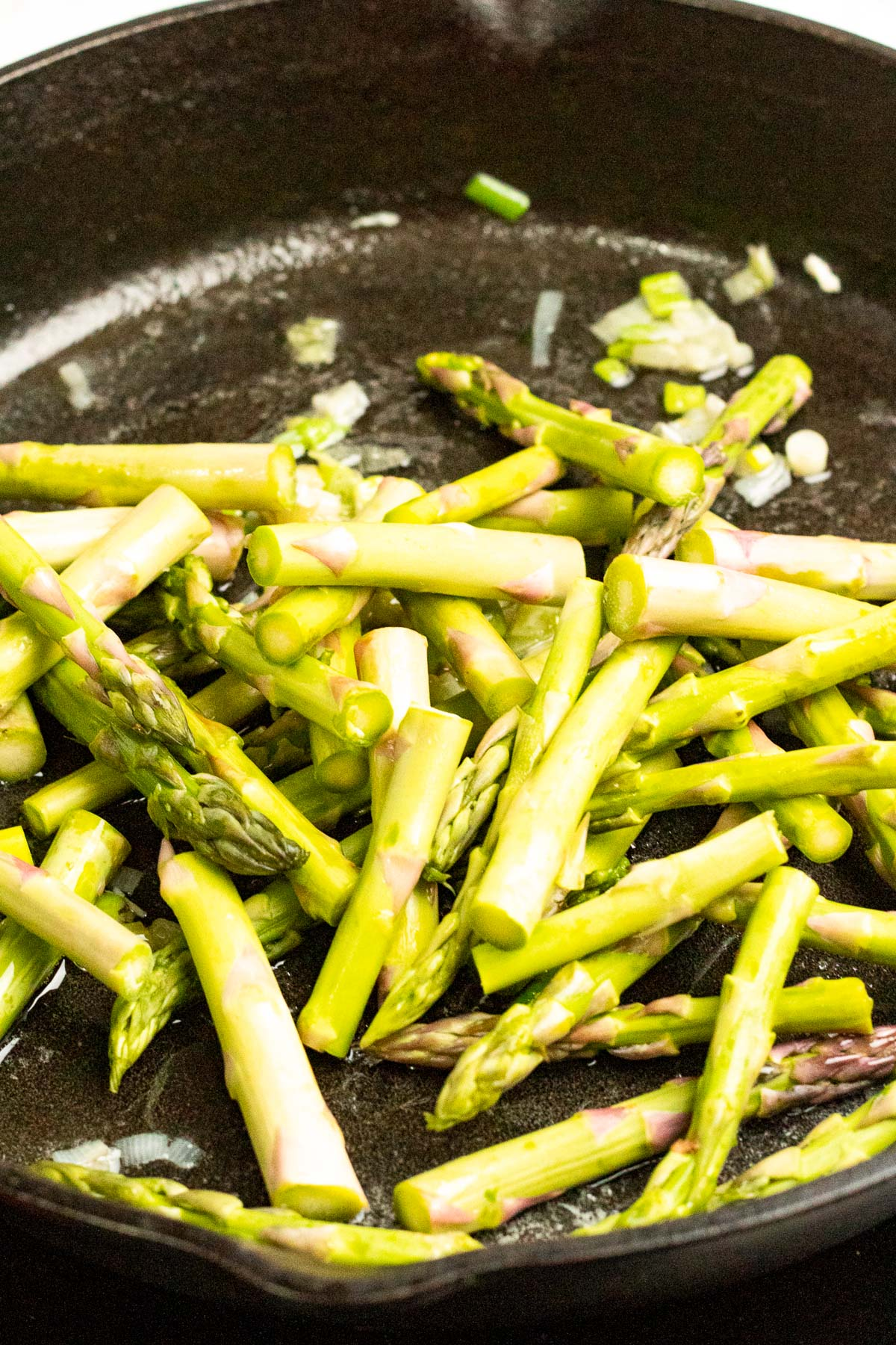 Sautéing asparagus in a pan.
