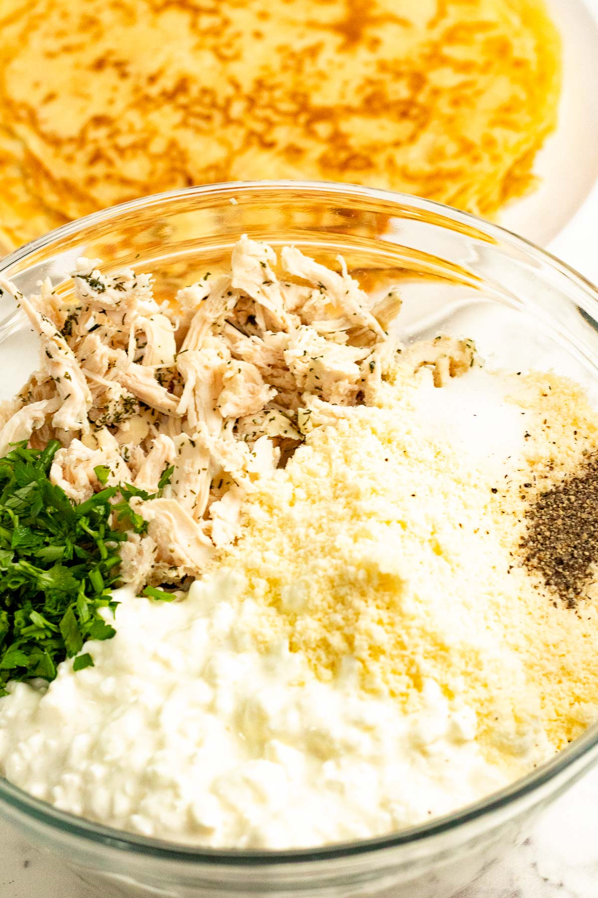 Savory chicken crepe filling ingredients in a bowl.