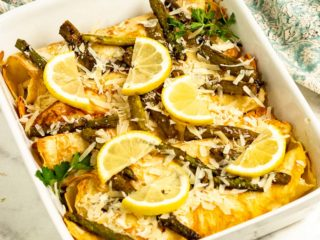 Baked chicken crepes in a baking dish topped with asparagus and lemon slices.