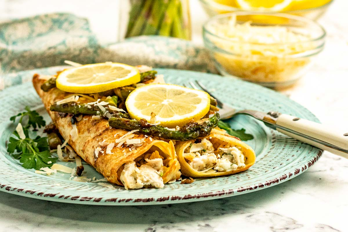 Savory crepes stuffed with chicken, served with asparagus and lemon slices.