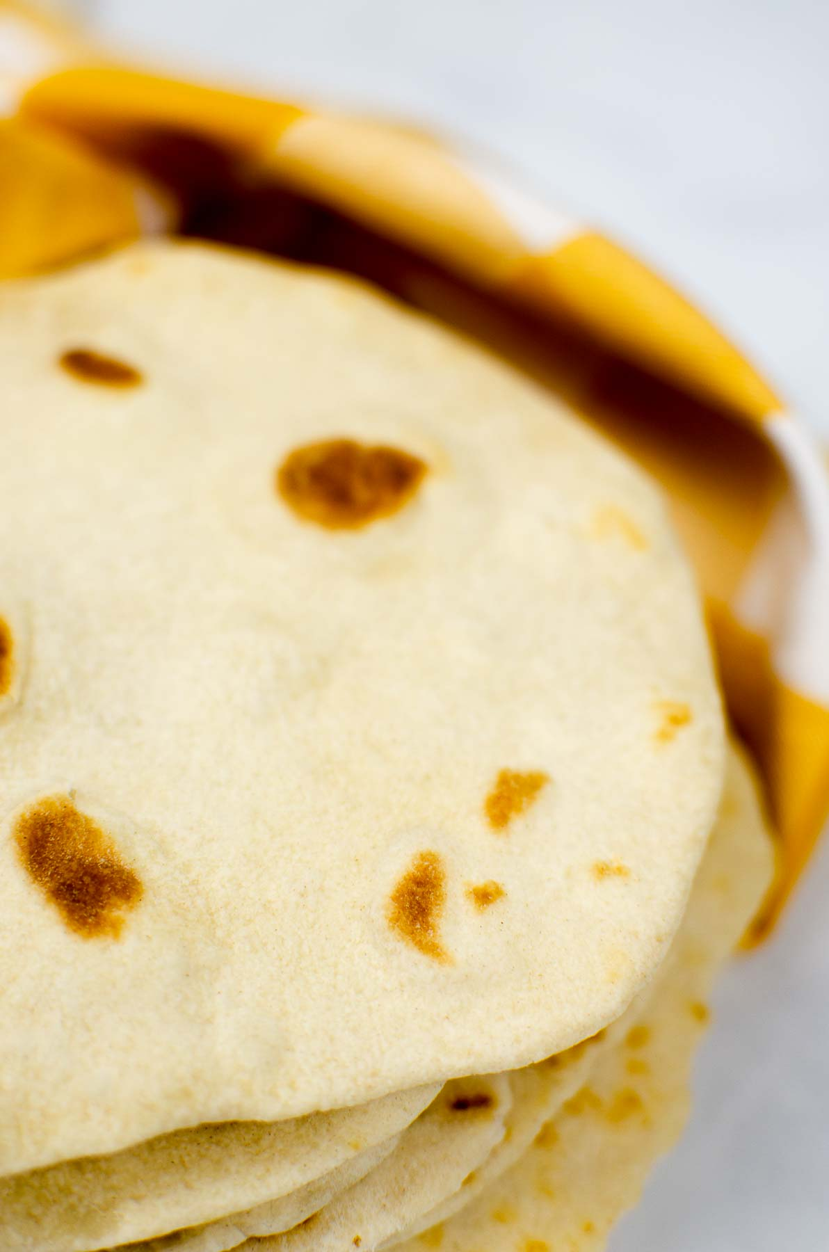 Flour tortillas wrapped in a yellow towel.