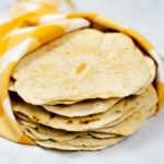 Stack of homemade flour tortillas wrapped in a towel.