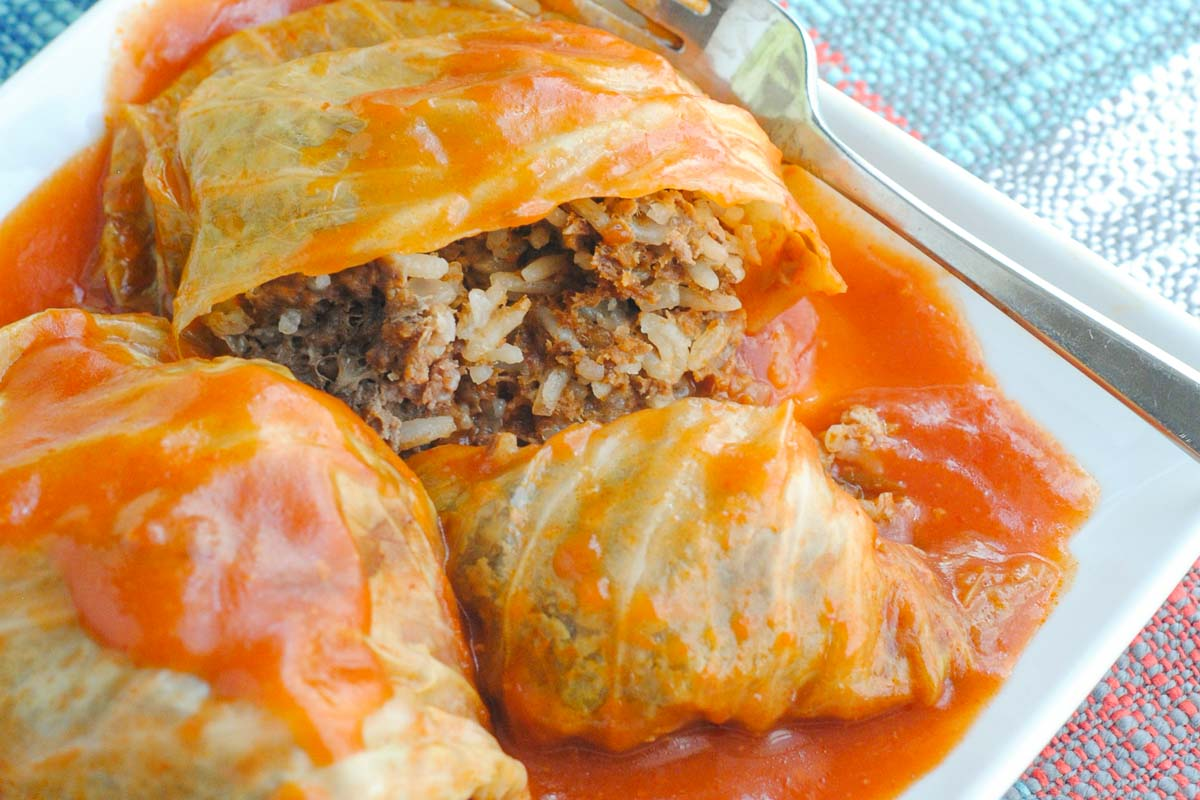 Russian Stuffed Cabbage Rolls on a plate with tomato sauce.