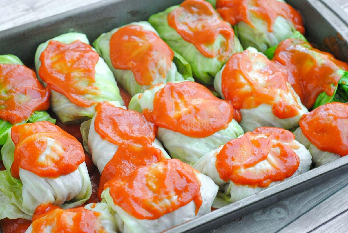 Pan of golubtsi with tomato sauce on top, ready to bake.