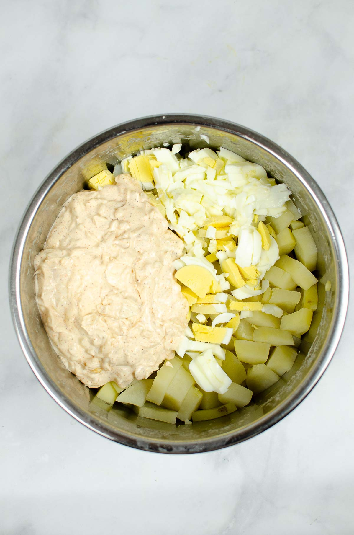 Chopped potatoes, eggs, and creamy dressing in the Instant Pot.