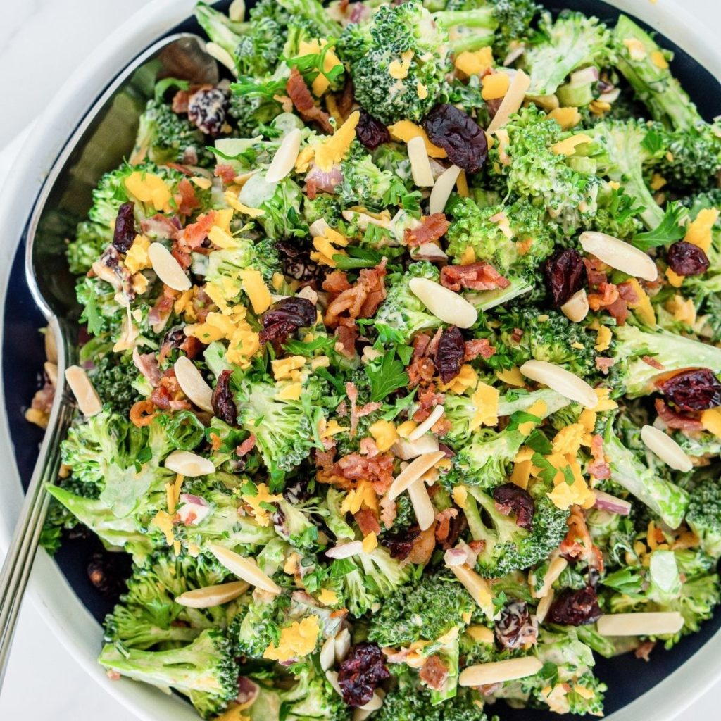 Bowl of broccoli bacon salad with cheddar, almonds, cranberries.
