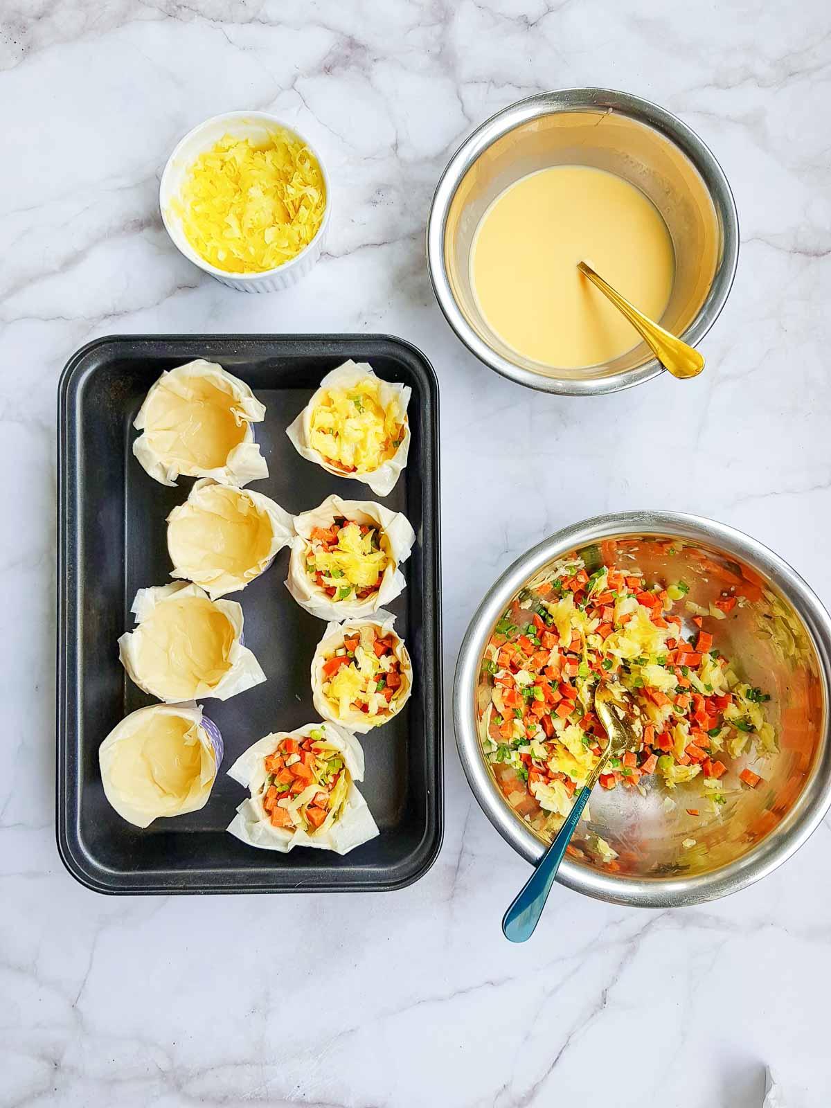 Adding quiche filling to phyllo dough quiche cups.