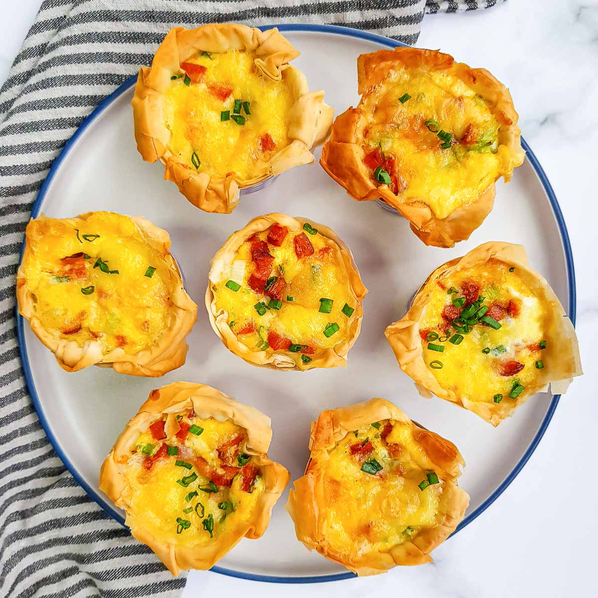 Mini phyllo quiches with sausage on a plate.