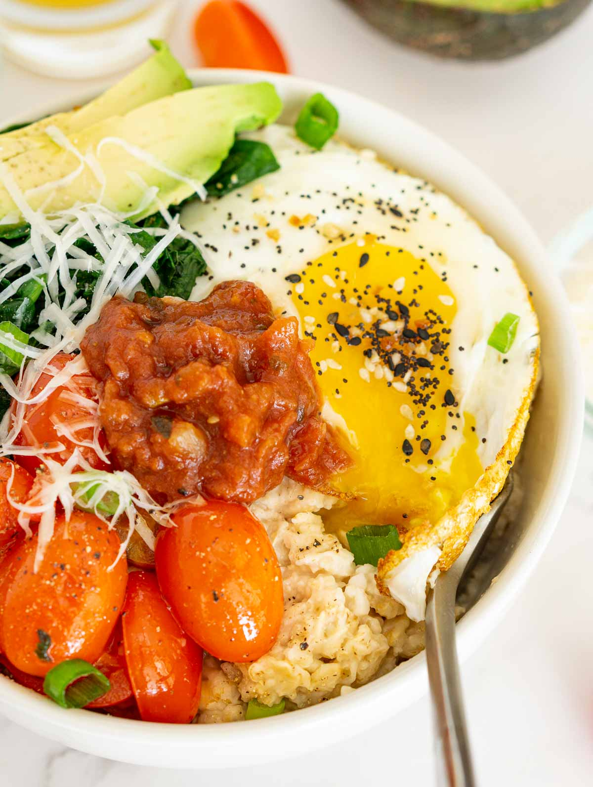 Savory oatmeal bowl with salsa and fried egg.