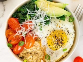 Bowl of savory oatmeal topped with fried egg, spinach, tomato, and avocado.