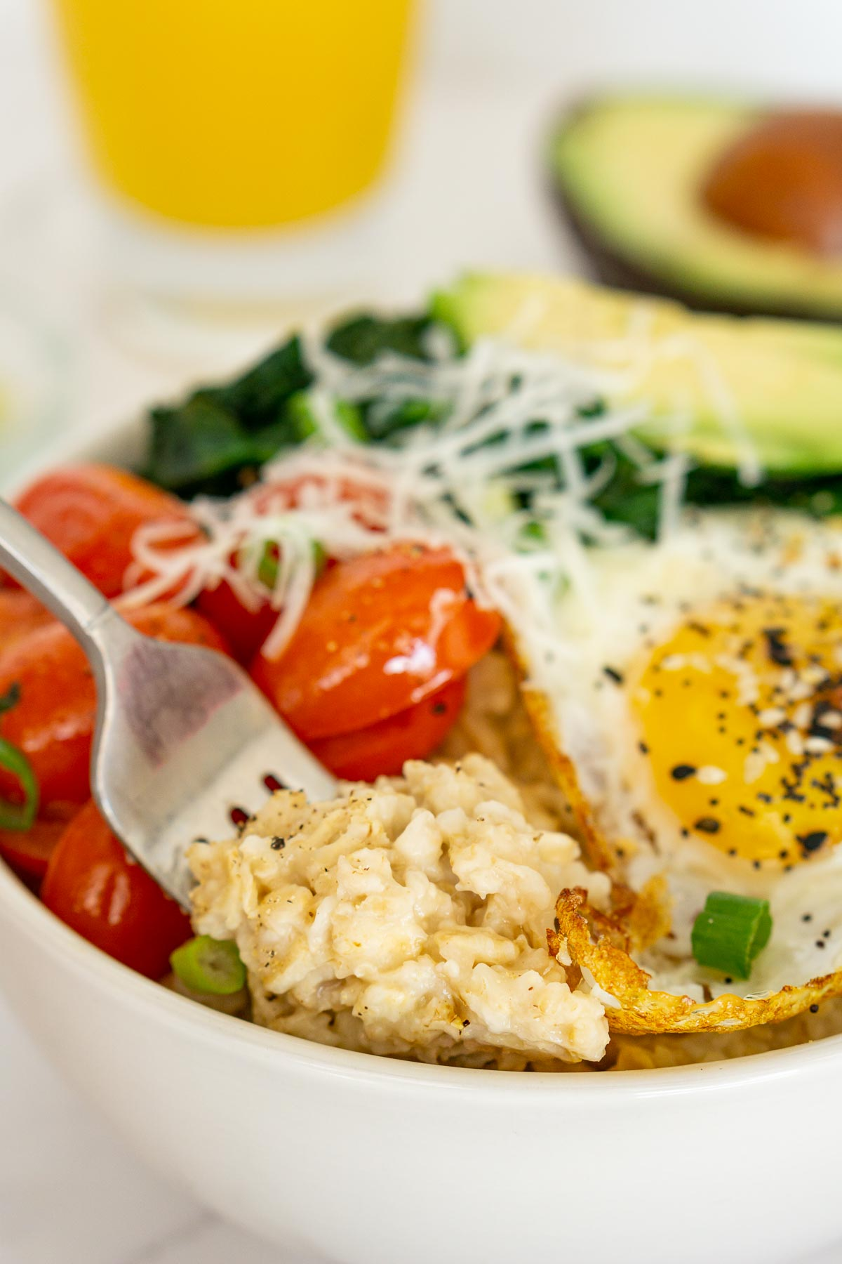 Savory oatmeal with eggs and veggies in a bowl.