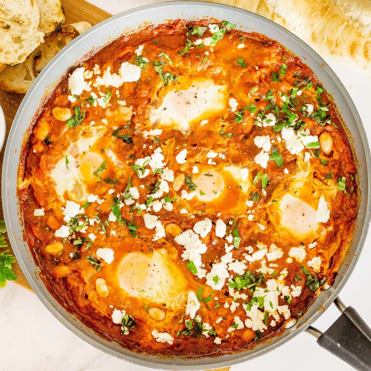 Shakshuka with feta and white beans in a skillet.