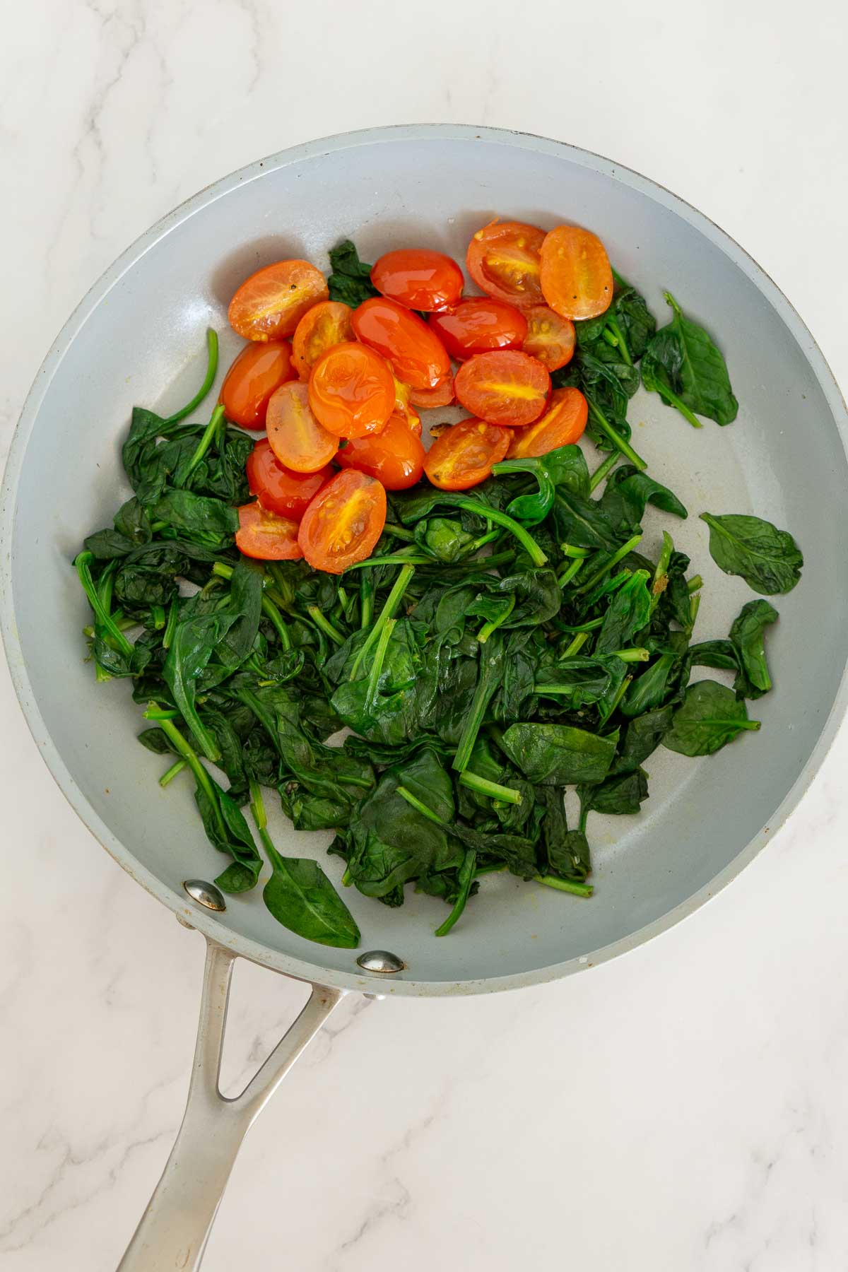 Sauteed spinach and grape tomatoes in a skillet.
