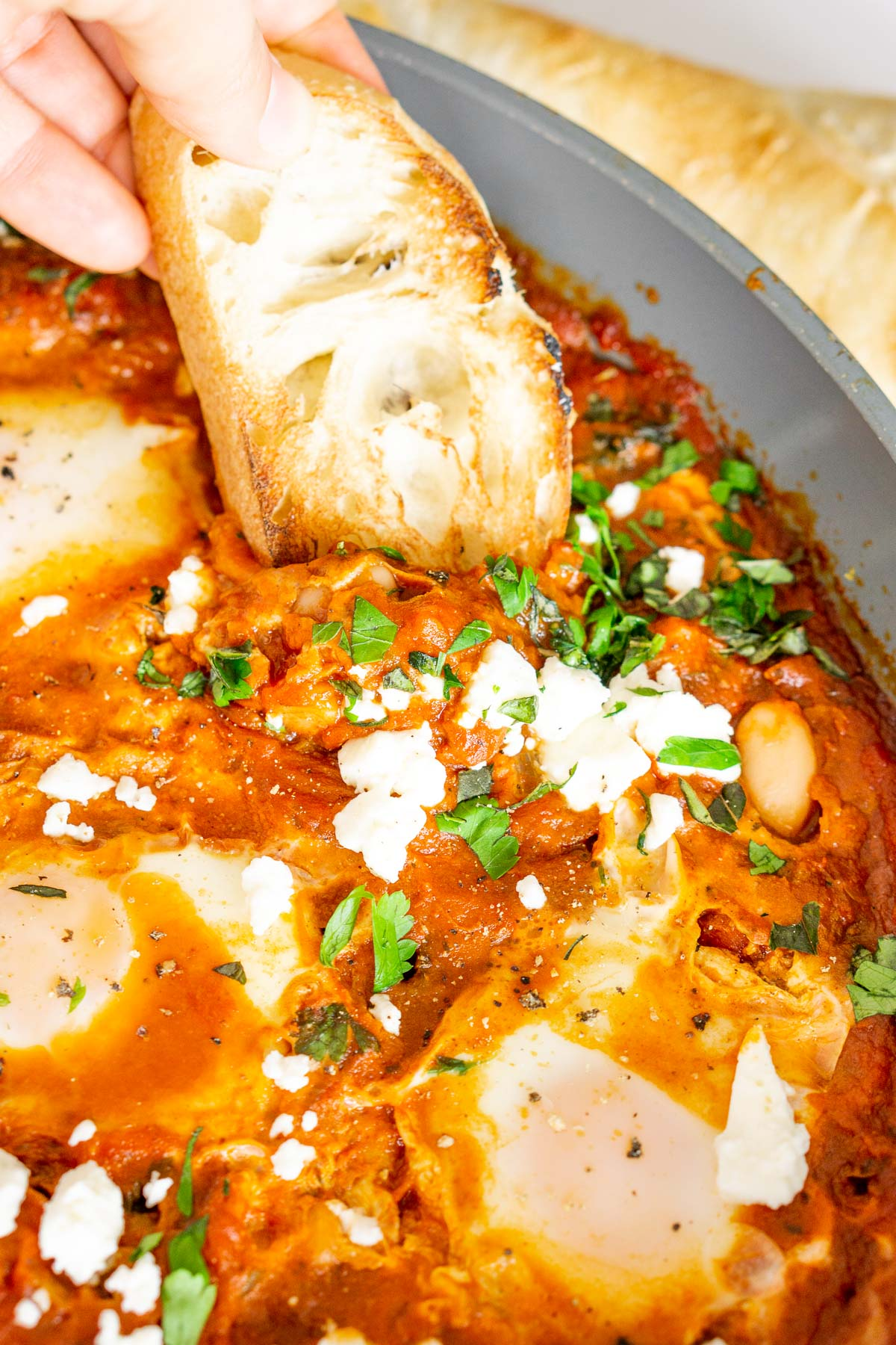 Dipping a toasted baguette into a white bean shakshuka with feta cheese.
