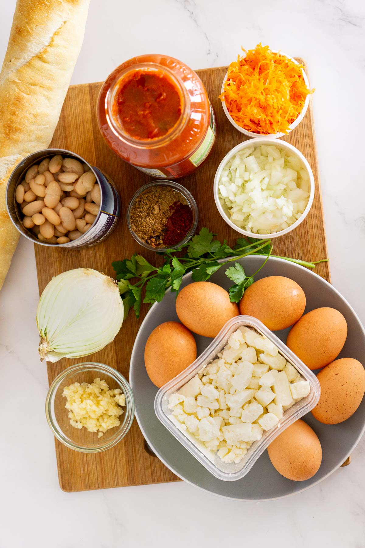 Ingredients to make shakshuka with feta and white beans.