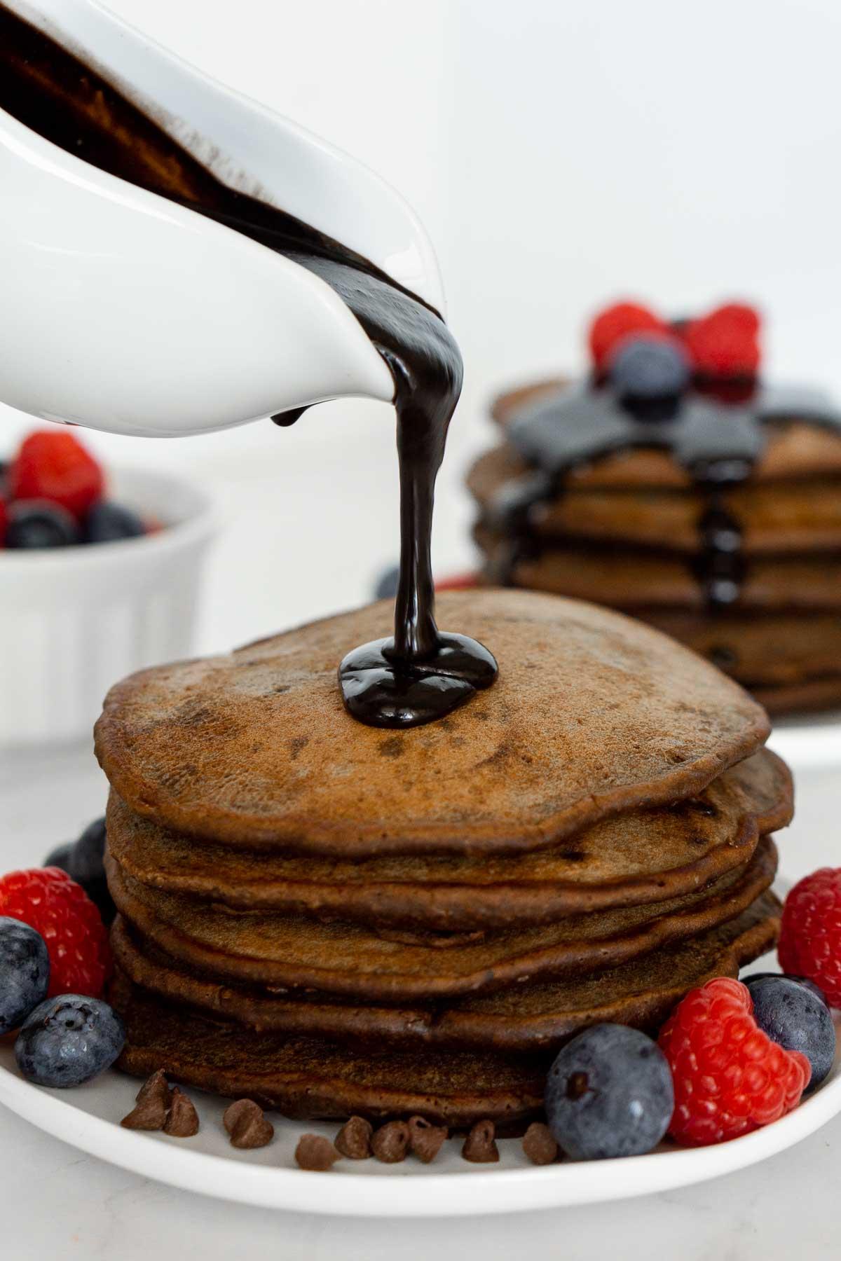Pouring chocolate sauce on pancakes.