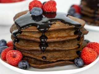 Stack of chocolate protein pancakes with chocolate sauce.