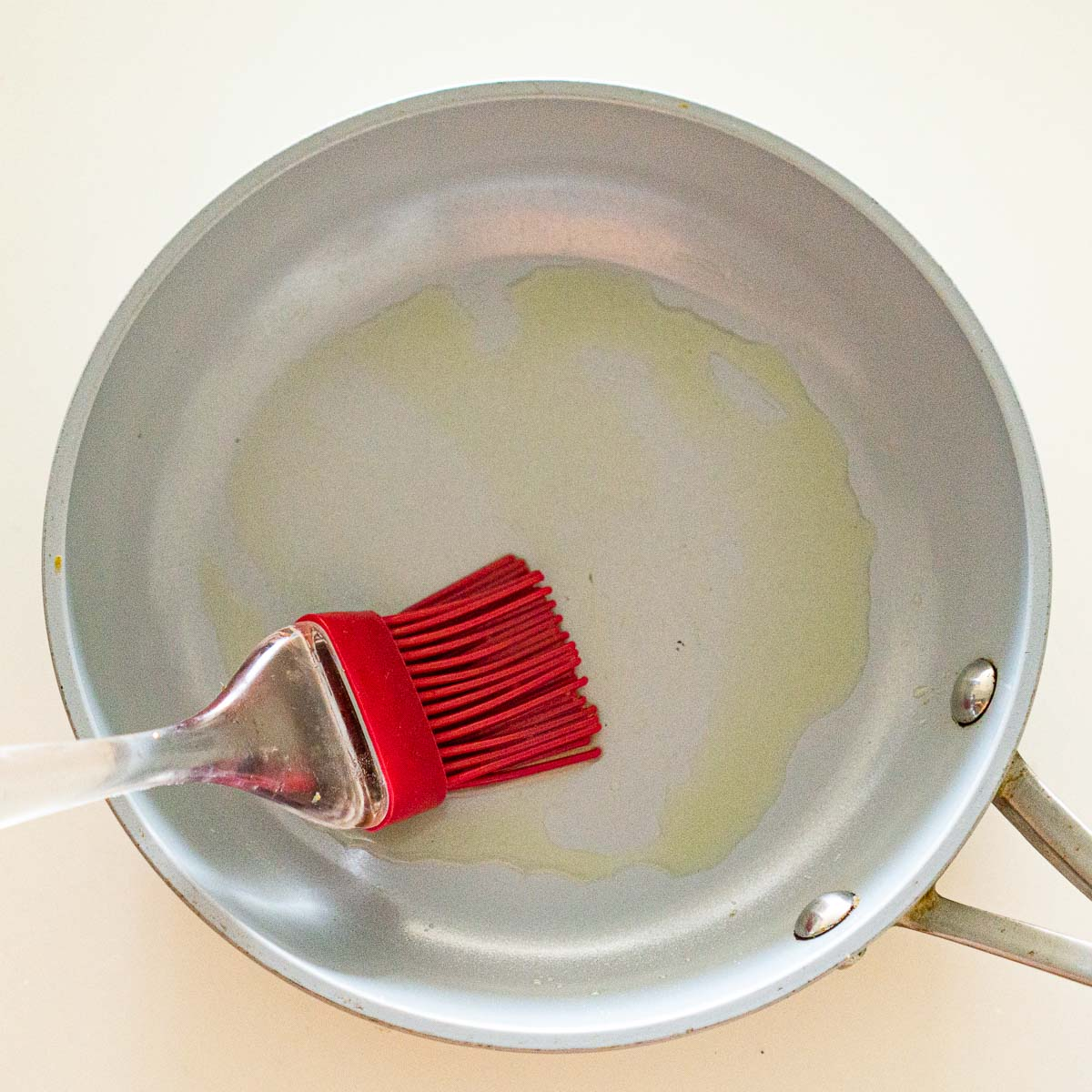 Brushing a non stick pan with oil.
