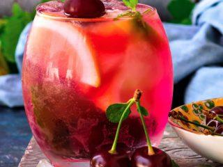 Cherry lemonade in a glass with cherry garnish.