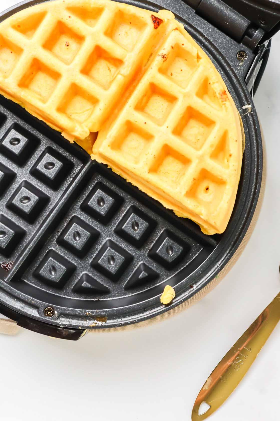 Half a waffle in a waffle iron.
