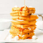 Stack of pumpkin waffles with marshmallows with syrup being poured on top.
