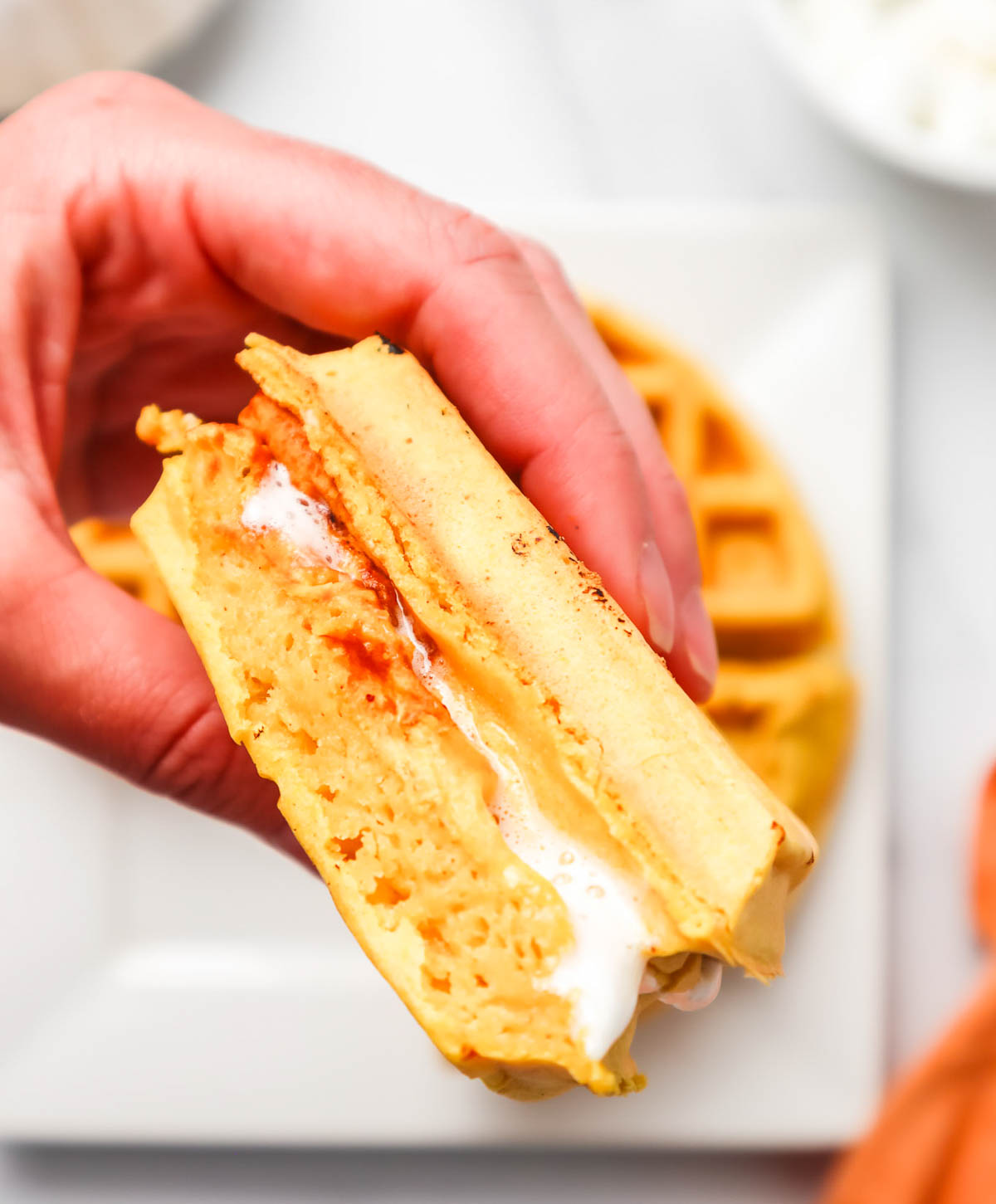 Hand holding a waffle sandwich with melted marshmallows.