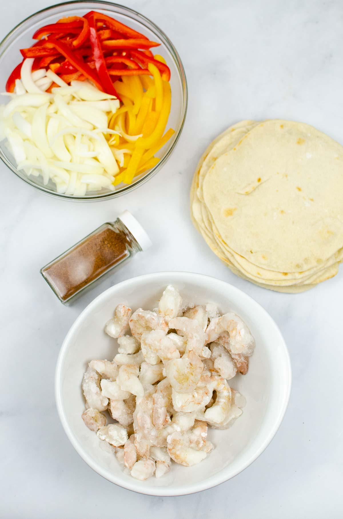 Ingredients for shrimp fajitas: sliced peppers, onions, shrimp, and fajita seasoning.