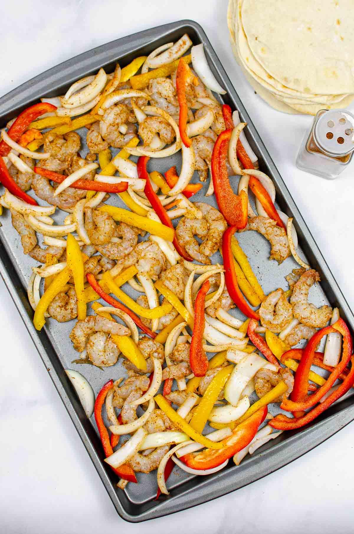 Sliced peppers, onions, and shrimp seasoned with fajita seasoning on a sheet pan.