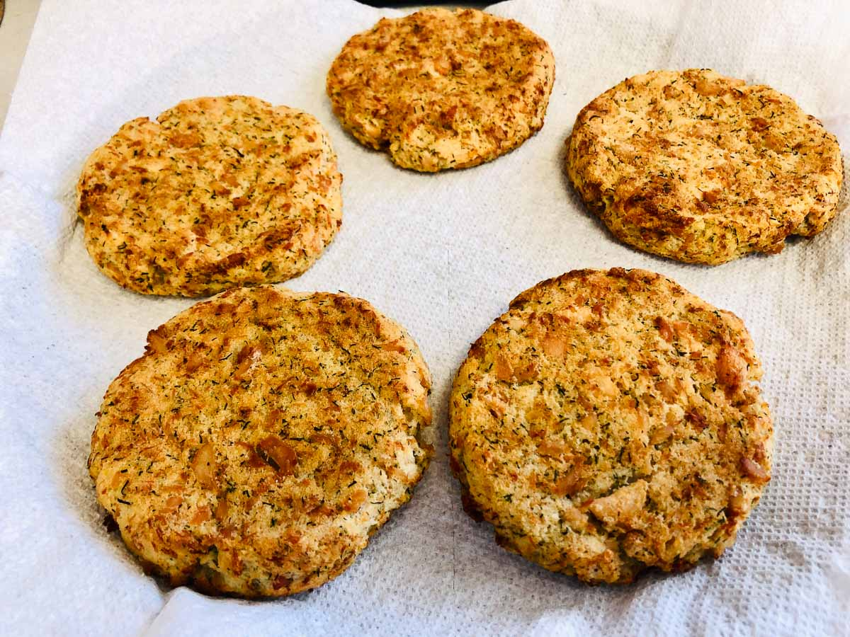 Cooked salmon potato cakes on a paper towel.