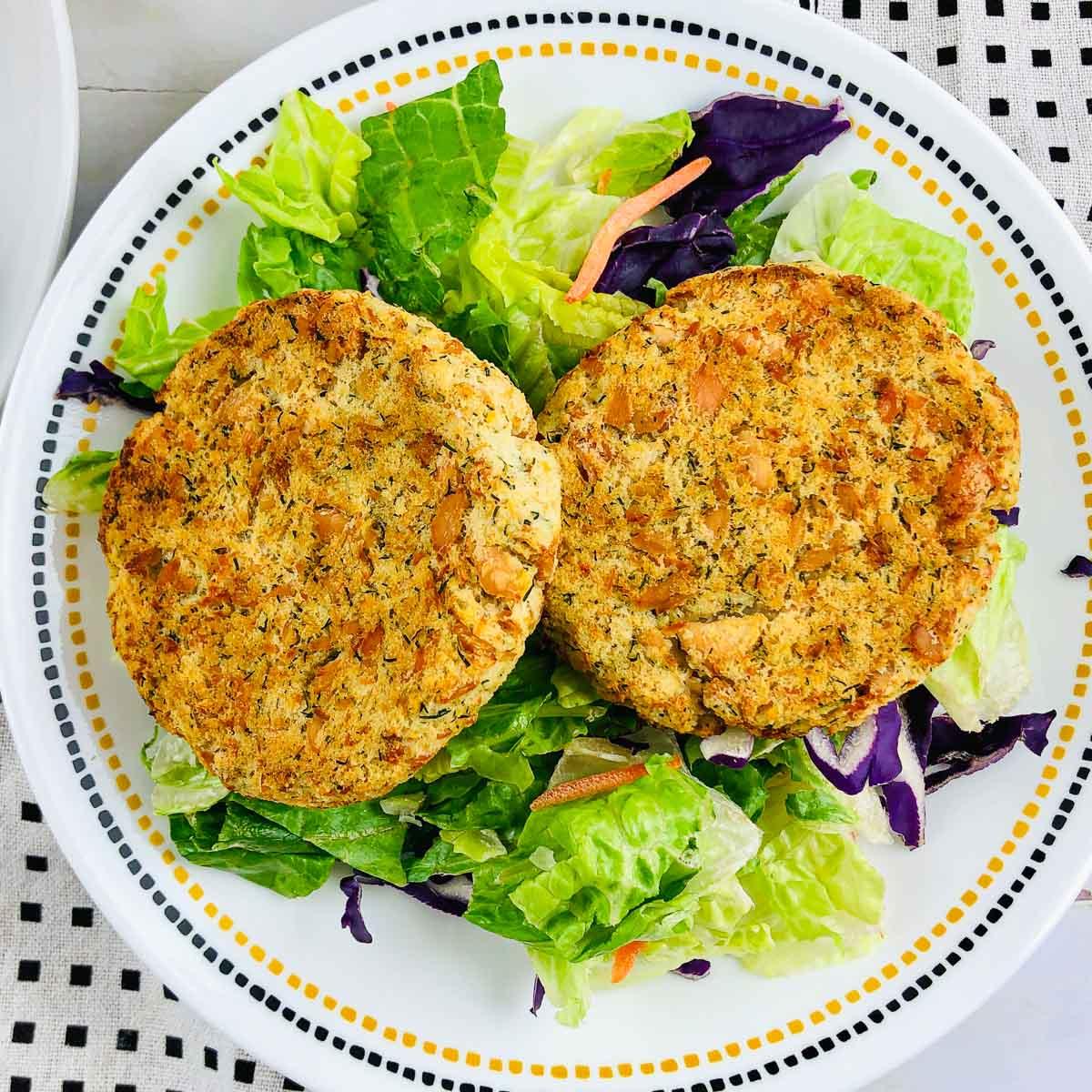 Two salmon potato patties over salad on a plate.